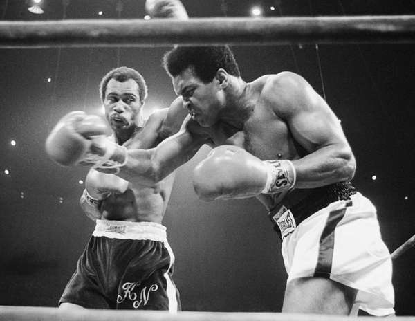 Muhammad Ali, right, winces as Ken Norton hits