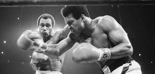 Muhammad Ali, right, winces as Ken Norton hits