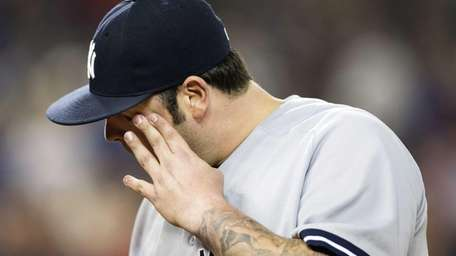 Yankees' Joba Chamberlain walks off the mound after