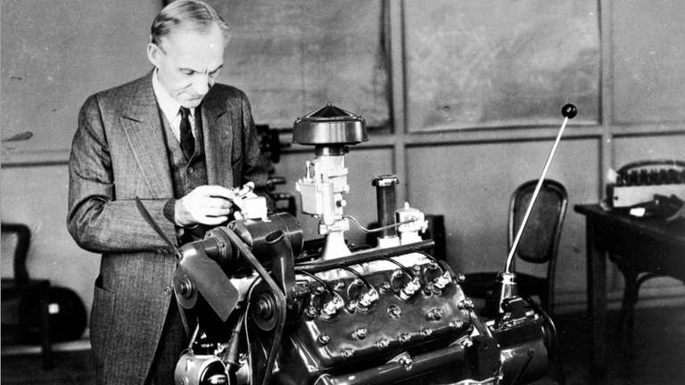 Henry Ford stands with the flathead V-8 engine