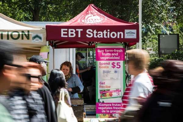 People walk past an Electronic Benefits Transfer (EBT)