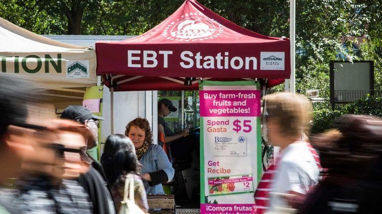 People walk past an Electronic Benefits Transfer (EBT)