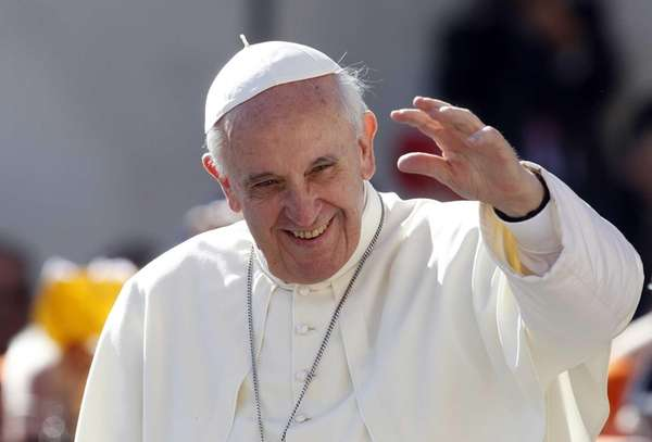 Pope Francis waves to faithful as he arrives