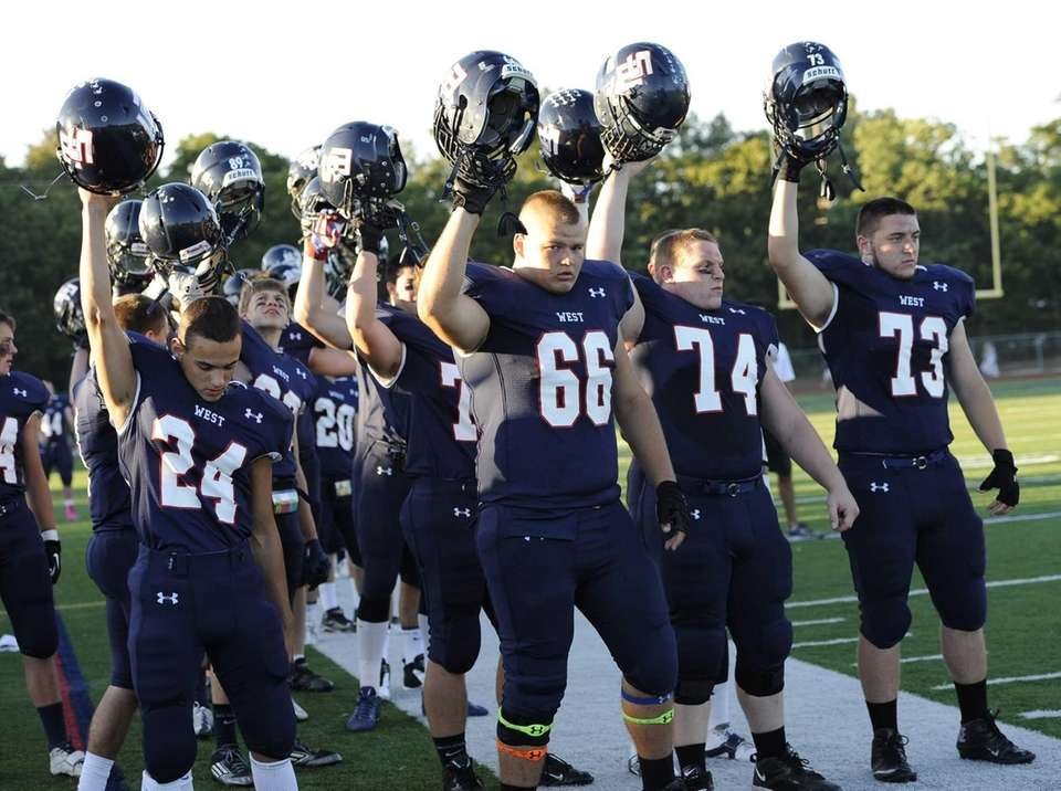 Smithtown West players raise their helmets before action