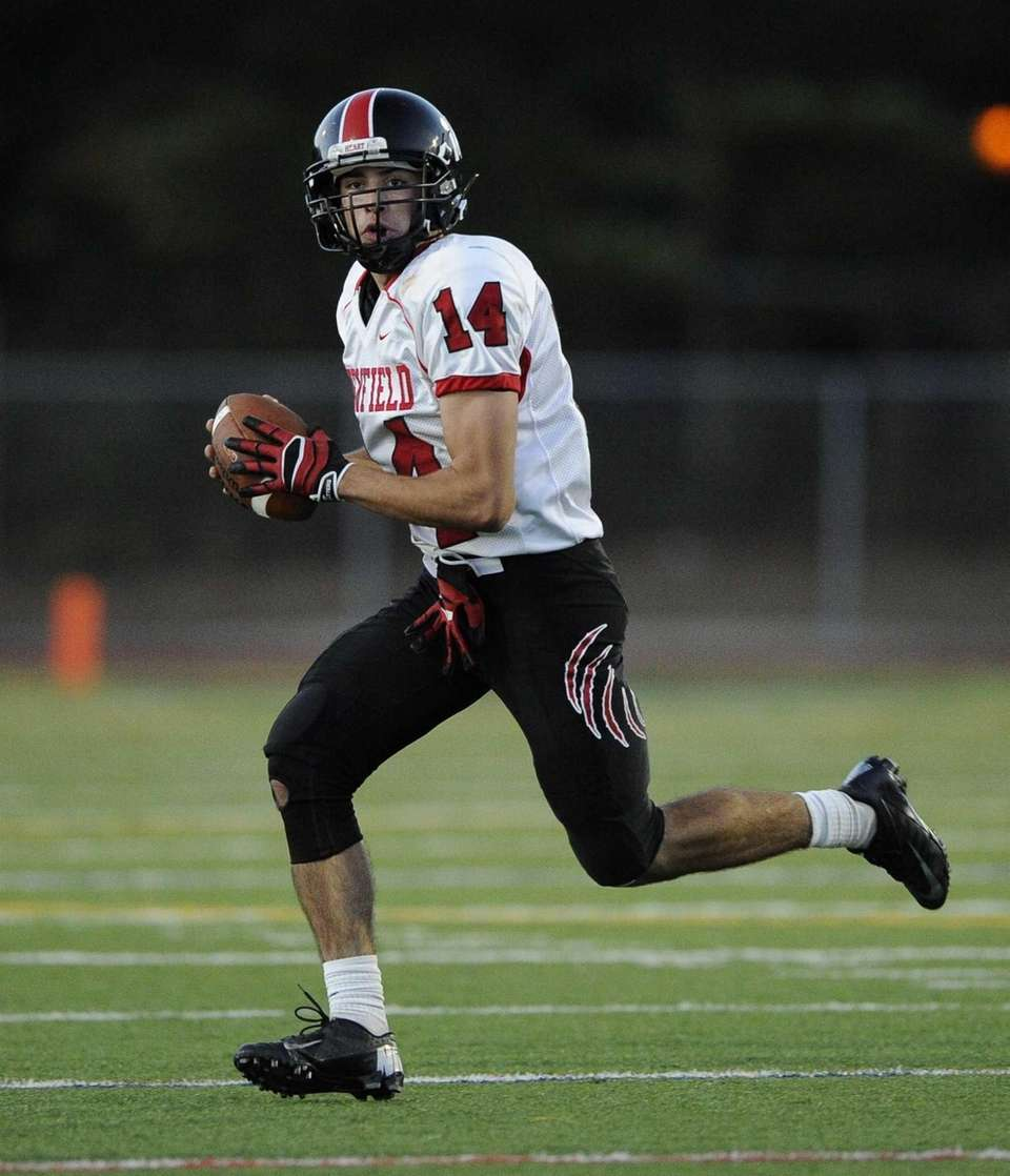 Newfield quarterback Dylan Harned scrambles with the football