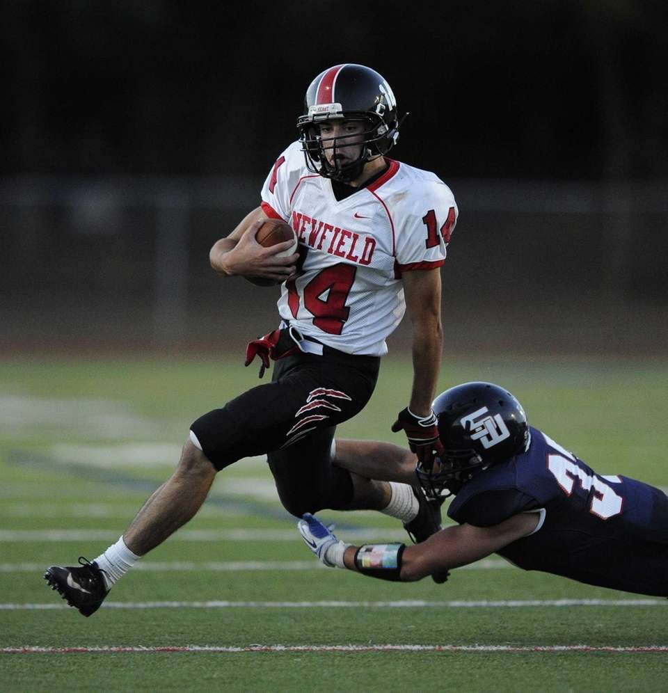 Newfield quarterback Dylan Harned breaks a tackle by