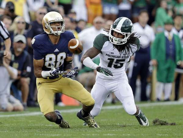 Notre Dame wide receiver Corey Robinson, left, makes