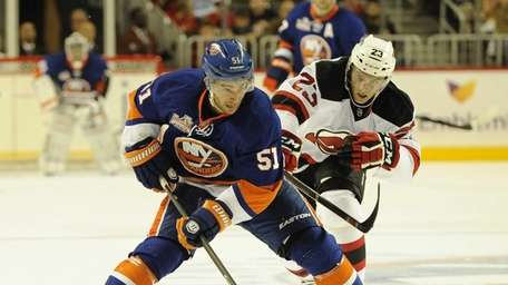 Islanders center Frans Nielsen is defended by New