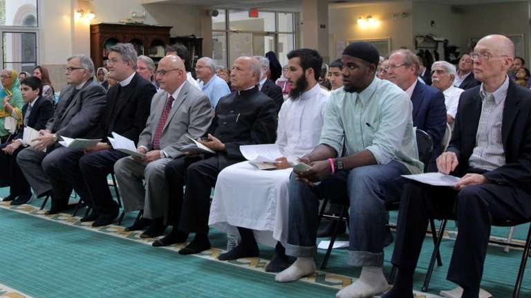 Speakers representing many faiths sit in the front