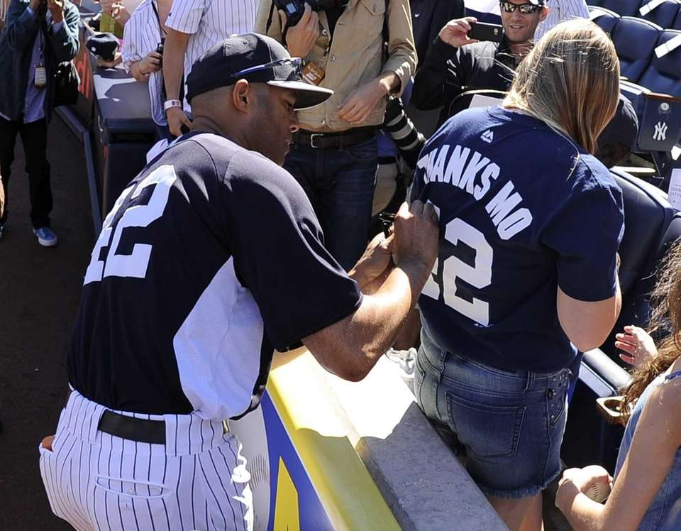 New York Yankees pitcher Mariano Rivera autographs a