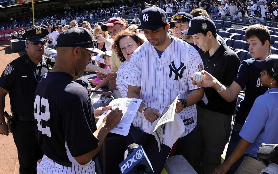 Yankees pitcher Mariano Rivera signs autographs for fans