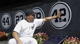 Yankees closer Mariano Rivera touches his plaque in
