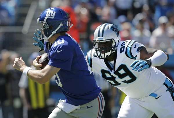 Giants quarterback Eli Manning (no. 10) scrambles past