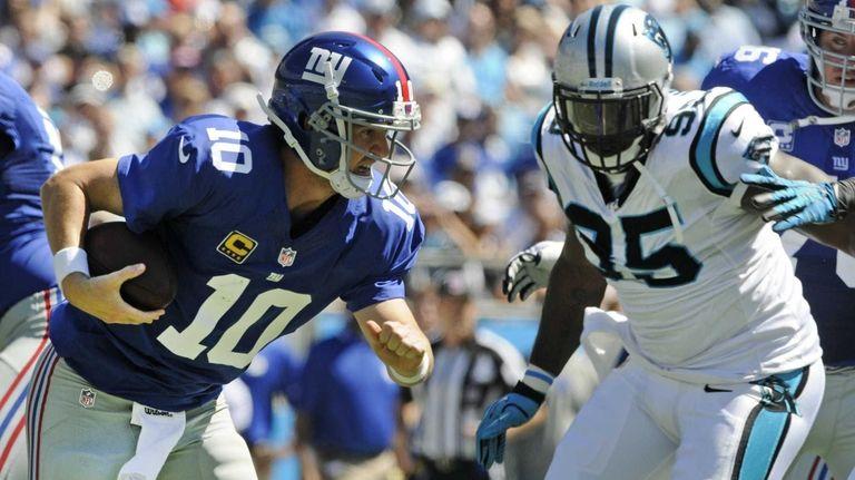 Giants quarterback Eli Manning tries to escape the
