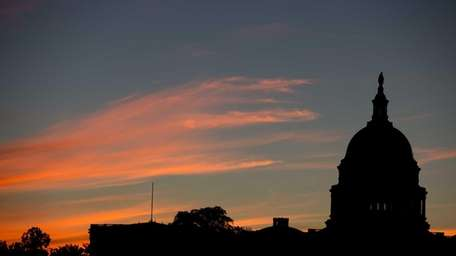The Capitol Dome is silhouetted by the sunrise.