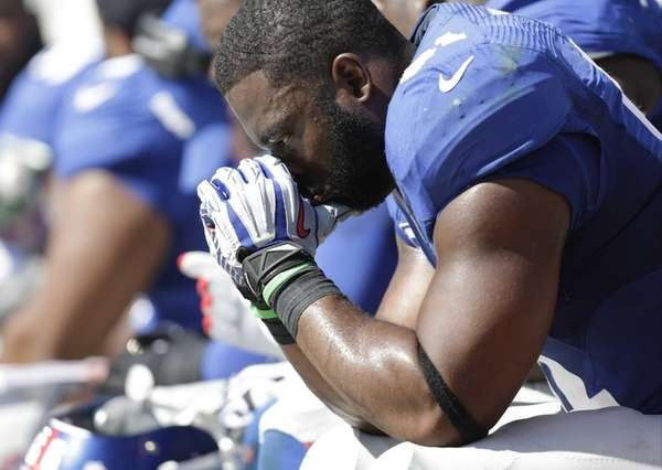 Justin Tuck sits on the bench during the