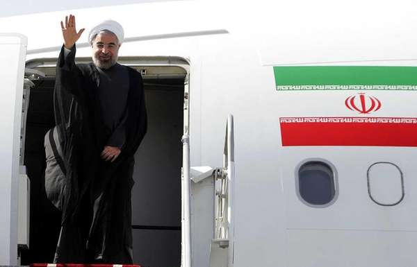 Iranian President Hassan Rowhani waves before entering an