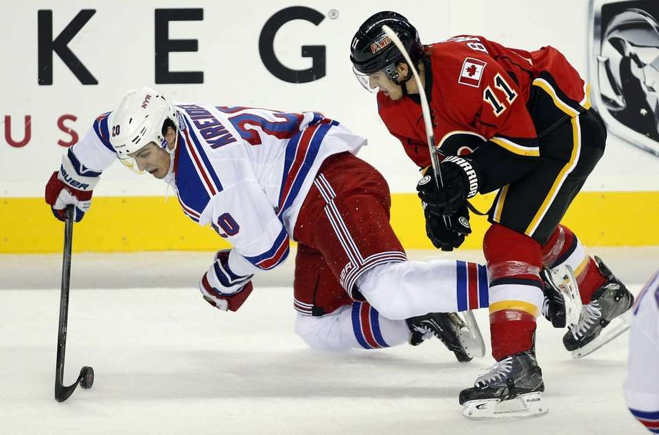 Chris Kreider, left, gets knocked to the ice
