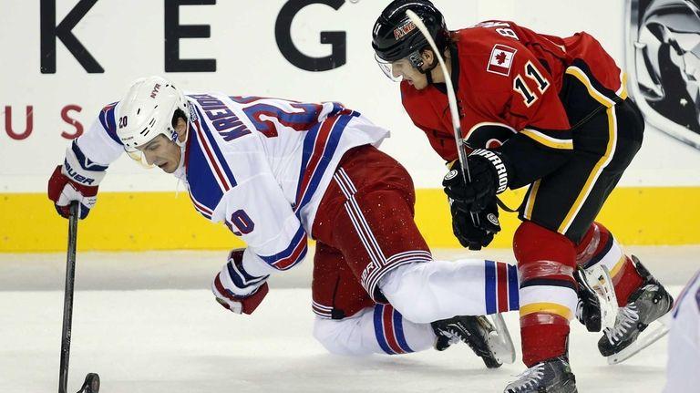 Chris Kreider, left, gets knocked to the ice