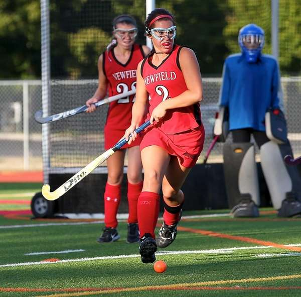 Newfield's Danielle Guttilla moves the ball out of