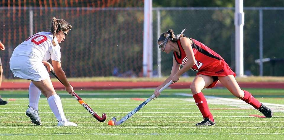 Newfield's Shannon Doherty, right, looks to clear the