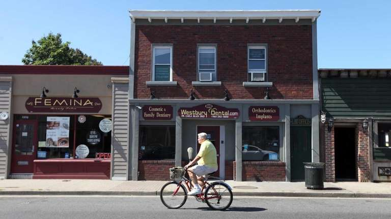 A man rides his bicycle down Post Avenue