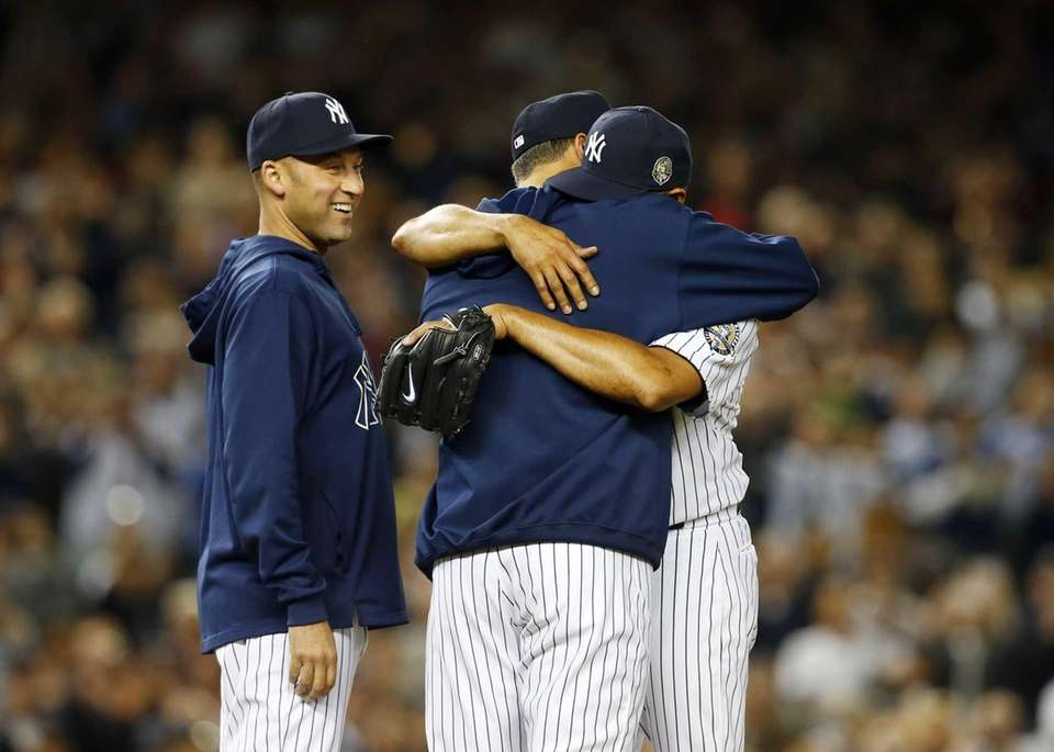 Mariano Rivera of the Yankees hugs teammate Andy