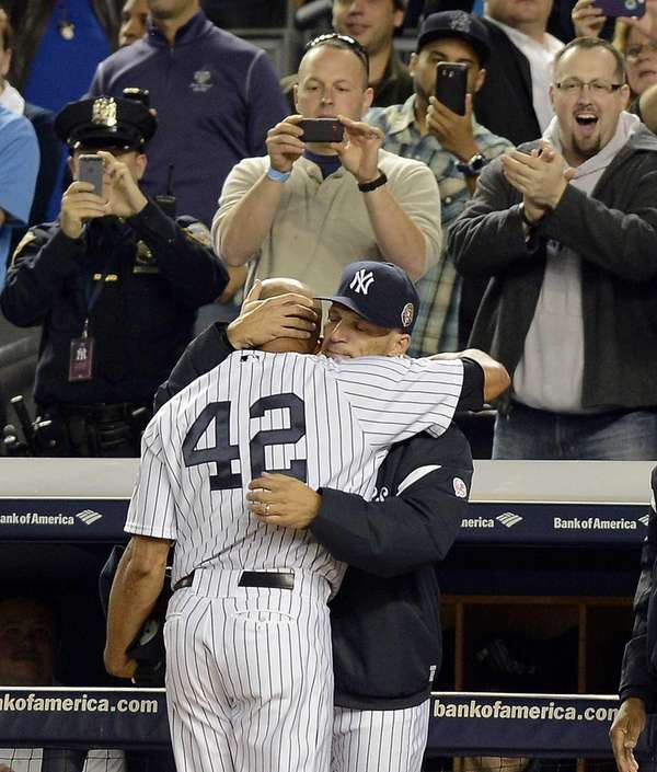 Yankees pitcher Mariano Rivera hugs Joe Girardi as