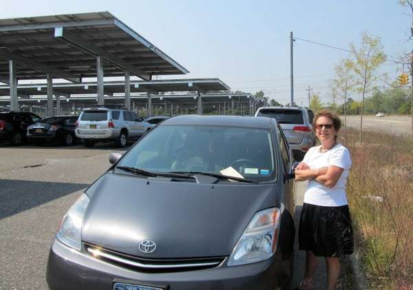 Carol Woodman stands next to a ticketed car,