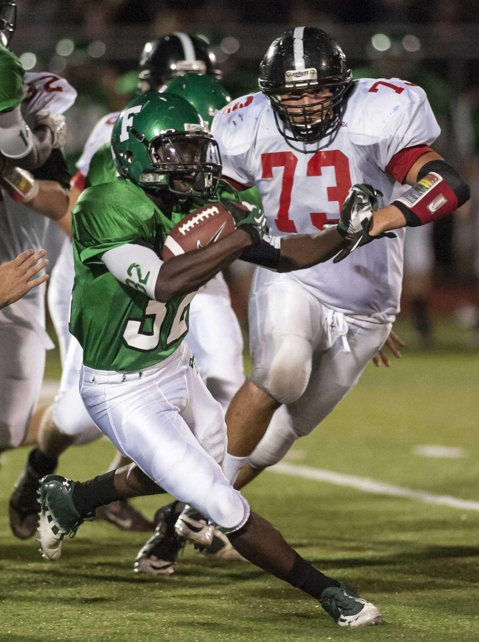 Farmingdale's Styvenson Hogarth, left, weaves his way through