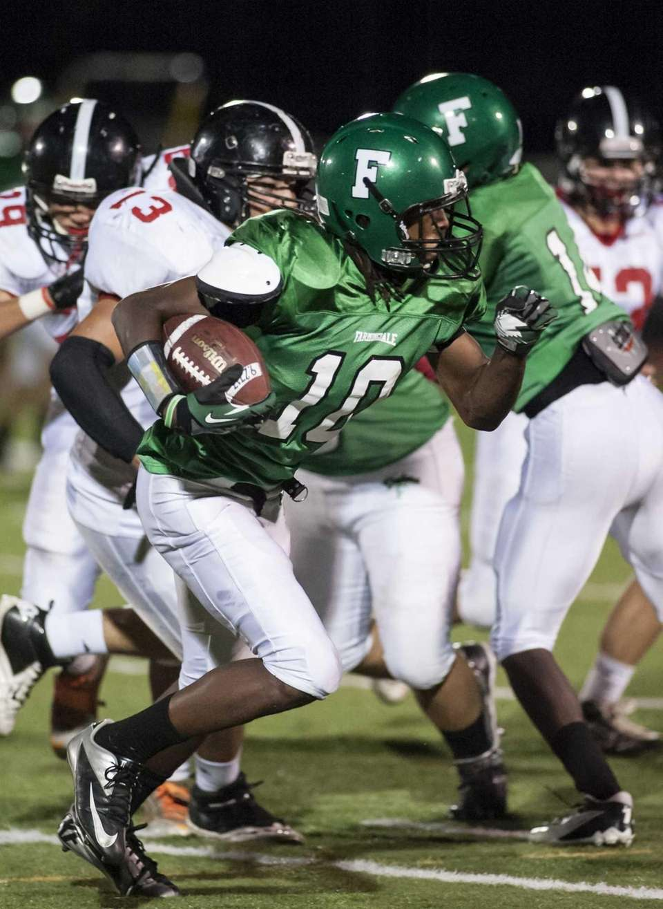Farmingdale's Curtis Jenkins runs for yardage against Syosset