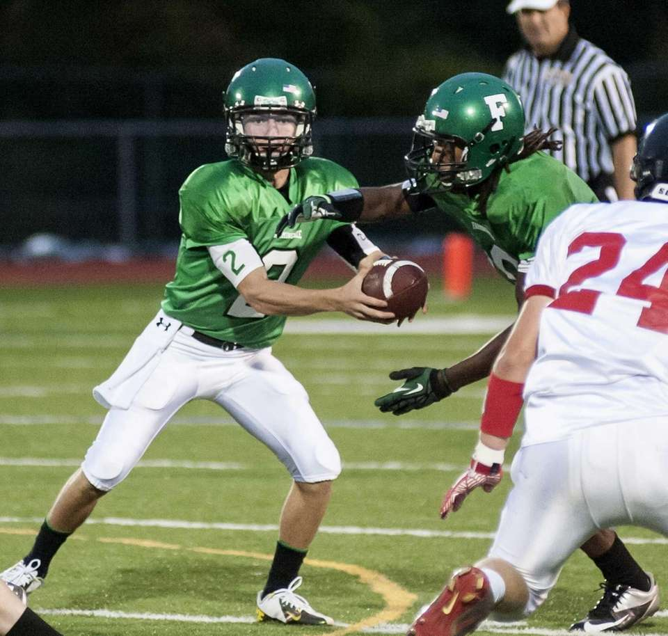 Farmingdale's Vinny Quinn, left, hands the ball off