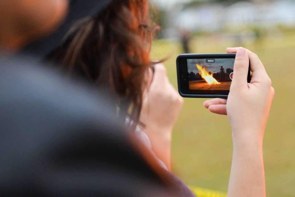 Students take video of the bonfire at John