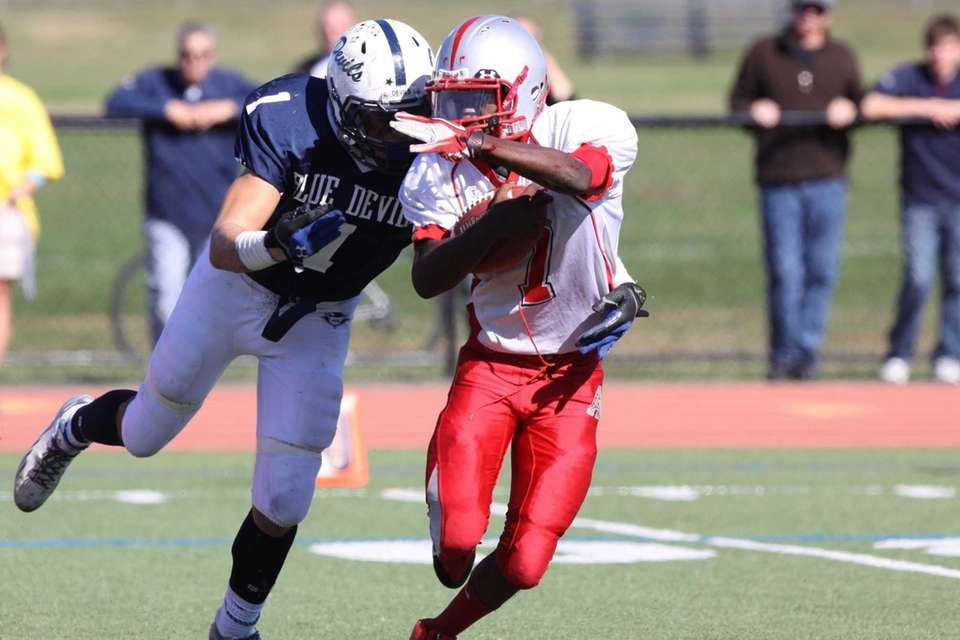 Amityville's Sean Walters, right, is tackled by Huntington's