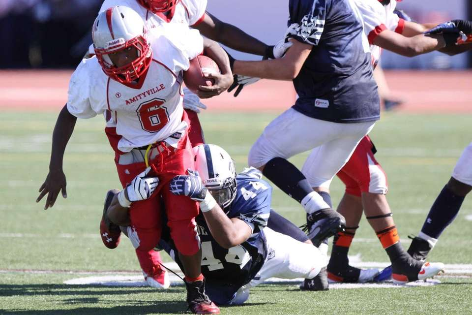 Amityville's Cameron Grady, left, is tackled by Huntington's