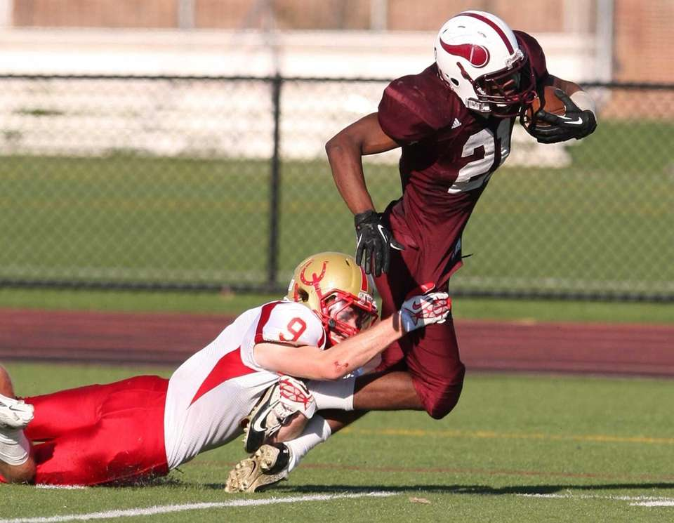 Bay Shore's Bradley Pierre, right, gets brought down