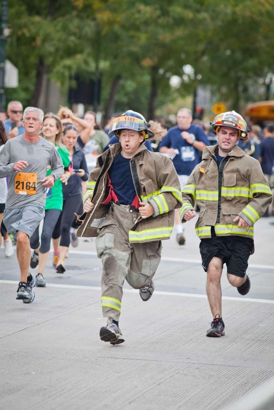 Two firefighters approach the finish line of the