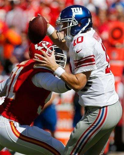 Eli Manning (10) avoids the rush by Kansas