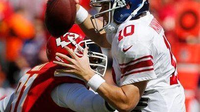Eli Manning (10) avoids the rush by Kansas