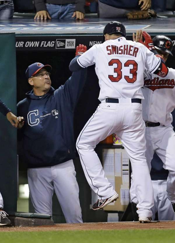 Cleveland Indians manager Terry Francona, left, slaps hands