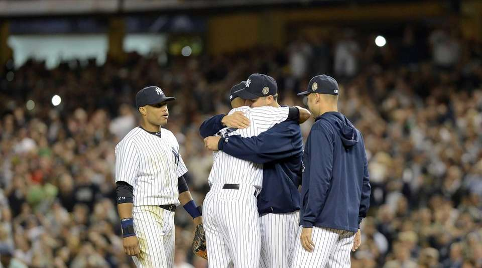 New York Yankees pitcher Mariano Rivera is hugged