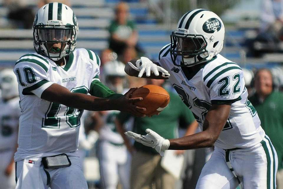 Holy Trinity quarterback Cameren Hayes (left) hands off