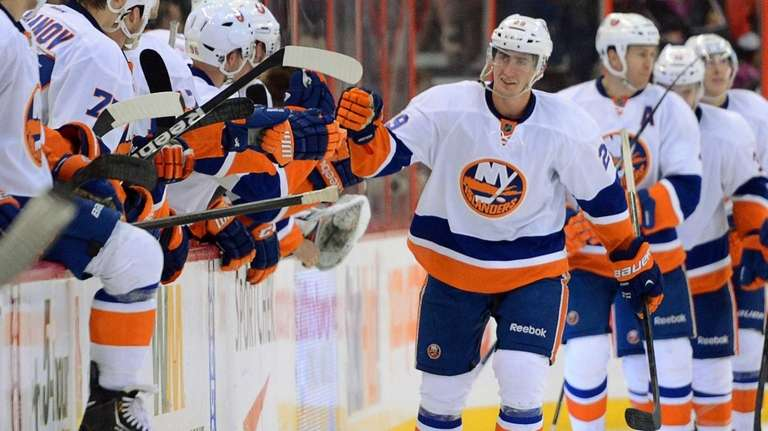 Islanders player Brock Nelson skates past the bench