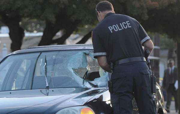 A Suffolk County police officer examines the damaged
