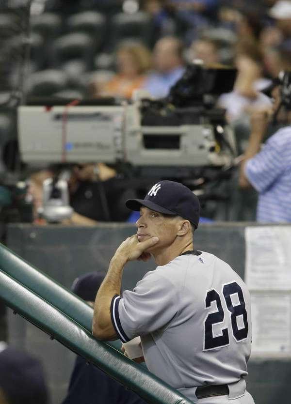 Joe Girardi watches the scoreboard from the dugout