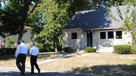 Suffolk County police detectives in front of home
