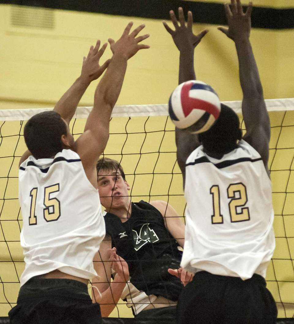 Bellmore JFK's Gary Anderson, center, watches his spiked