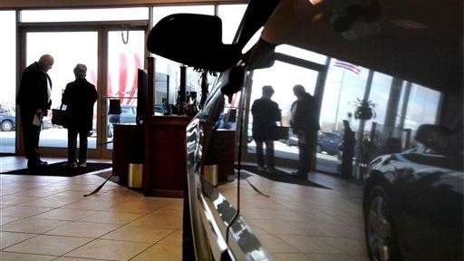 A car salesman speaks with a customer at