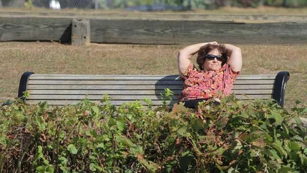 A woman takes in the sun at Heckscher