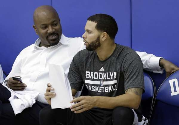 Nets general manager Billy King, left, speaks with
